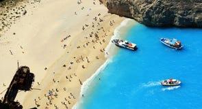 Turistas en la playa de la arena de Navagio Zakynthos Grecia Foto de archivo