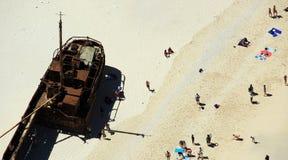 Turistas en la playa de la arena de Navagio Zakynthos Grecia Foto de archivo libre de regalías