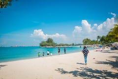 Turistas en la playa de Siloso, isla de Sentosa, Singapur foto de archivo
