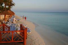 Turistas en la playa en el amanecer Imágenes de archivo libres de regalías