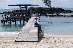 Turistas en la playa que espera para ir el practicar surf de la cometa imagen de archivo