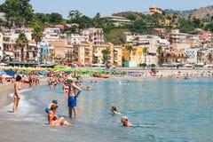 Turistas en la playa urbana en la ciudad de Giardini Naxos Foto de archivo