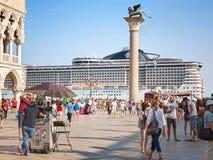 Turistas en la Plaza de San Marcos en Venecia, y barco de cruceros MSC Preziosa Foto de archivo libre de regalías