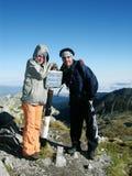 Turistas en la tapa de montañas imagen de archivo