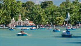 Turistas en los barcos en el lago cerca del monumento al timelapse de Alfonso XII en el Parque del Buen Retiro - parque del agrad almacen de video
