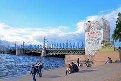 Turistas en los pasos del embarcadero en el fondo de banderas de Fotos de archivo libres de regalías