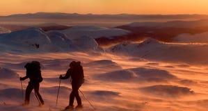 Turistas en montañas en una puesta del sol Fotografía de archivo libre de regalías