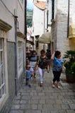 Turistas en poca calle tipical en la ciudad vieja de Dubrovnik Fotos de archivo