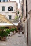 Turistas en poca calle tipical en la ciudad vieja de Dubrovnik Imágenes de archivo libres de regalías