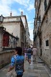 Turistas en Tipical poca calle en la ciudad vieja de Dubrovnik, Croacia Foto de archivo libre de regalías