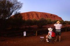 Turistas en un amanecer en la montaña. Imagen de archivo