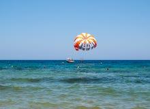 Turistas en un paracaídas sobre la playa en Malia Crete, Grecia fotos de archivo