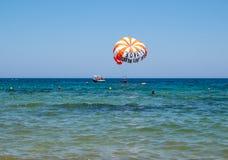 Turistas en un paracaídas sobre la playa en Malia Crete, Grecia imágenes de archivo libres de regalías