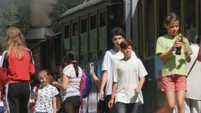 Turistas en una estación de tren que se prepara para un viaje de las vacaciones con un tren viejo del vapor almacen de video