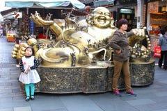Turistas en una estatua de risa de Buda en la calle vieja de Hefang, Hangzhou, China Imagen de archivo