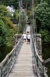 Turistas en una pasarela de la suspensión Imagenes de archivo