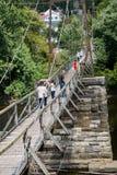 Turistas en una pasarela de la suspensión Fotos de archivo libres de regalías