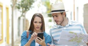 Turistas enojados que usan un teléfono elegante estropeado almacen de metraje de vídeo