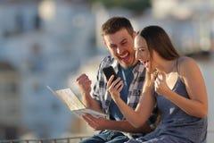 Turistas entusiasmados que encontram a melhor oferta em um telefone esperto foto de stock royalty free