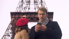 Turistas estrangeiros que olham o mapa em linha no smartphone que procura por vistas em Paris filme
