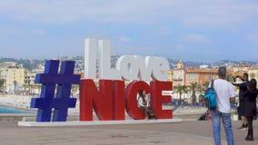 Turistas extranjeros que hacen las fotos cerca de la inscripción conmemorativa grande sobre amor a Niza metrajes
