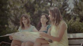 Turistas fêmeas com mapa que discutem sobre lugar do curso video estoque