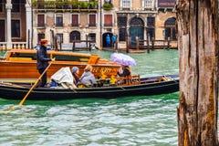 Turistas fêmeas em um passeio famoso do barco da gôndola durante a chuva na cidade com o chapéu de palha vestindo do gondoleiro,  foto de stock royalty free