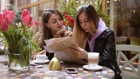 Turistas fêmeas novos - de cabelos compridos na roupa ocasional que lê o mapa da cidade no café exterior Beber caucasiano das men filme