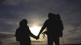 Turistas felices de la familia que caminan sosteniendo la silueta de la mano en la puesta del sol Concepto del viaje de la forma  almacen de metraje de vídeo