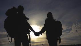 Turistas felices de la familia que caminan sosteniendo la silueta de la mano en la puesta del sol concepto del viaje del trabajo  almacen de metraje de vídeo