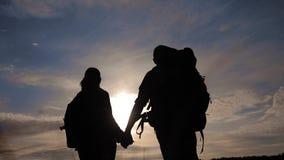Turistas felices de la familia que caminan sosteniendo la silueta de la mano en la puesta del sol concepto del viaje del trabajo  metrajes