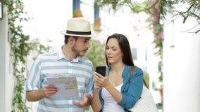 Turistas felices que caminan comprobando el contenido del teléfono de vacaciones metrajes