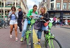 Turistas femeninos en las bicis en Amsterdam, Holanda Foto de archivo