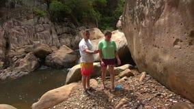 Turistas Guy Girl Examine Large Boulder por el río en parque almacen de video