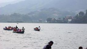Turistas indianos nos barcos de enfileiramento no lago contra o contexto da cidade da montanha video estoque