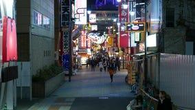 Turistas japoneses de Sightseeng en el centro de la ciudad de Osaka en la noche almacen de metraje de vídeo