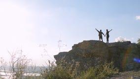 Turistas jovenes con las mochilas que disfrutan de la opinión del valle del top de la montaña Levante para arriba mis manos metrajes