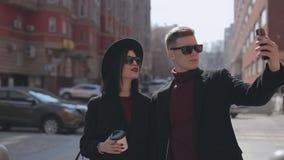 Turistas jovenes elegantes de los pares que hacen el selfie en calle de la ciudad almacen de metraje de vídeo