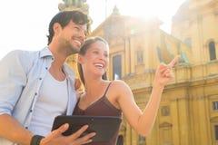 Turistas jovenes en ciudad con la tableta Imagen de archivo libre de regalías