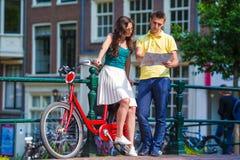 Turistas jovenes en las bicis que miran el mapa en europeo Fotografía de archivo