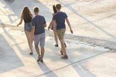 Turistas jovenes que caminan abajo de la calle imagen de archivo