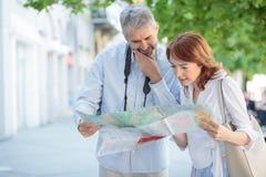 Turistas maduros s?rios que andam a calha a cidade, olhando o mapa para encontrar sentidos imagem de stock royalty free