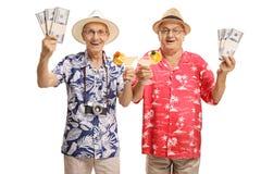 Turistas mayores con los cócteles y los paquetes del dinero Imágenes de archivo libres de regalías