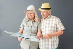 Turistas mayores en la situación del estudio de los sombreros de la playa aislados en el destino que elige gris en la sonrisa del imagenes de archivo