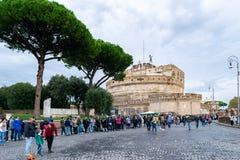 Turistas na linha sob os pinhos de pedra para visitar Castel Sant 'Angelo Mausoleum de Hadrian - castelo do anjo santamente fotos de stock