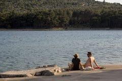 Turistas na praia na ilha Cres no mar de adriático, Croácia Fotos de Stock Royalty Free