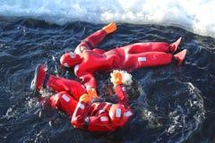 Turistas no identificados adaptados para arriba con una nadada del hielo del traje de la supervivencia en el mar Báltico congelad Fotografía de archivo