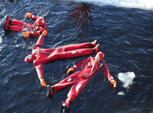 Turistas no identificados adaptados para arriba con una nadada del hielo del traje de la supervivencia en el mar Báltico congelad Imágenes de archivo libres de regalías