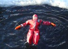 Turistas no identificados adaptados para arriba con una nadada del hielo del traje de la supervivencia en el mar Báltico congelad Foto de archivo libre de regalías