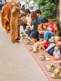 Turistas no identificados que ofrecen el arroz pegajoso al monje budista adentro imagen de archivo libre de regalías